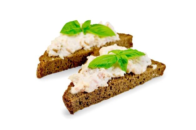 Kanapki na dwóch kawałkach chleba żytniego z kremem z łososia i majonezem, bazylia, izolowana na białym tle