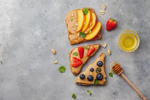 Kanapki orzechowe z miodem, miętą, jagodami, nektarynką i truskawką