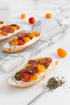 Kanapki pod dużym kątem z twarogiem i pomidorami na marmurowym blacie