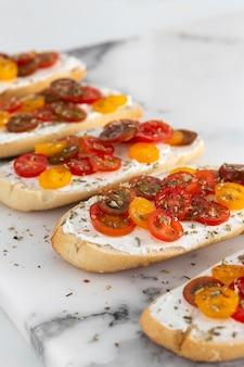 Kanapki pod dużym kątem z twarogiem i pomidorami na marmurze