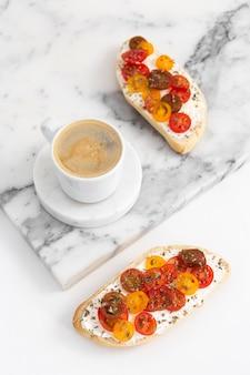 Kanapki pod wysokim kątem z twarogiem i pomidorami z filiżanką kawy