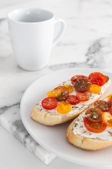 Kanapki pod wysokim kątem z twarogiem i pomidorami z kubkiem