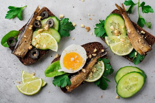 Kanapki rybne ze szprotkami, ogórkiem, limonką, gotowanymi jajkami, liśćmi pietruszki i mango na chlebie żytnim na szarej, starej betonowej powierzchni. selektywna ostrość