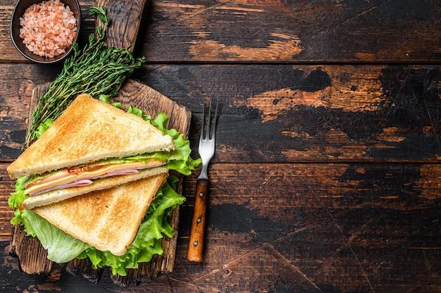 Kanapki turcja ham club z serem, pomidorami i sałatą na drewnianej desce do krojenia. ciemne drewniane tło.