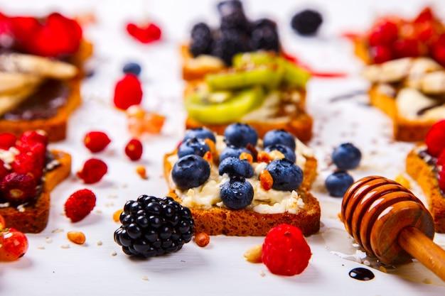 Kanapki ustaw słodko ze śmietaną i świeżymi jagodami