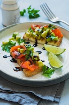 Kanapki z awokado i łososiem z sosem balsamicznym i kolendrą na starej desce z oliwek