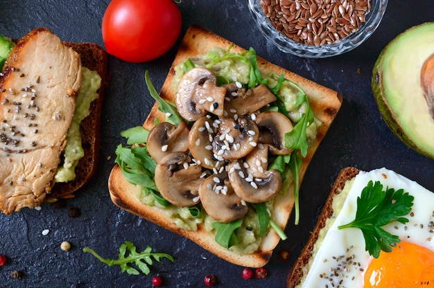 Kanapki z awokado, pieczarkami, rukolą, sezamem na czarnym stole. pyszna zdrowa przekąska z awokado. szybkie śniadania. koncepcja zdrowego odżywiania. odpowiednie odżywianie. widok z góry.