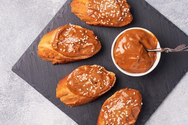 Kanapki z bagietką pieczywa posmarowaną słodką pastą z gotowanego mleka zagęszczonego.