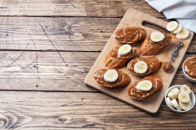 Kanapki z bagietką pieczywa smarowane słodką pastą gotowanego skondensowanego mleka i banana. drewniany stół. skopiuj miejsce