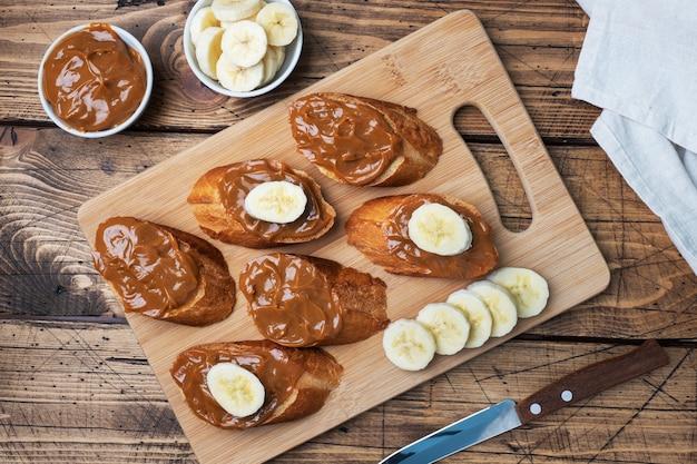 Kanapki z bagietką pieczywa smarowane słodką pastą gotowanego skondensowanego mleka i banana. drewniany stół.