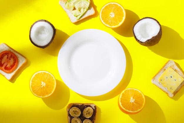 Kanapki z bananem, pomidorem, awokado, serem i świeżymi owocami, pomarańczą, kokosem i pustym białym talerzem na żółtym tle. pojęcie zdrowego śniadania, witamin, diety. leżał płasko, widok z góry.
