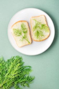 Kanapki z białego chleba i świeżego koperku na talerzu i kilka koperków na zielonym tle. zioła witaminowe w zdrowej diecie. widok z góry i z pionu