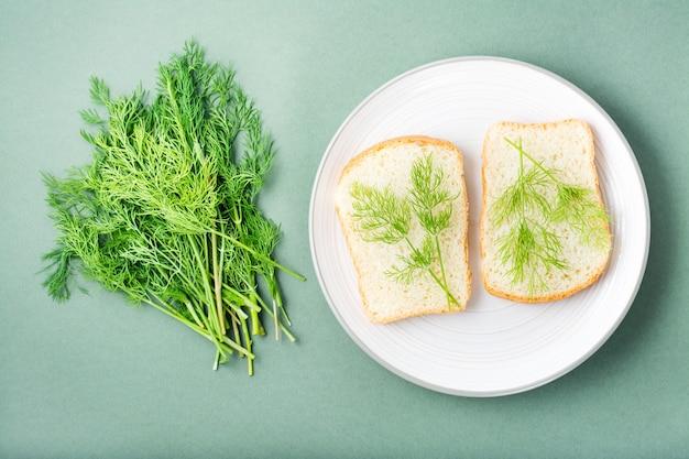 Kanapki z białego chleba i świeżego koperku na talerzu i kilka koperków na zielonym tle. zioła witaminowe w zdrowej diecie. widok z góry