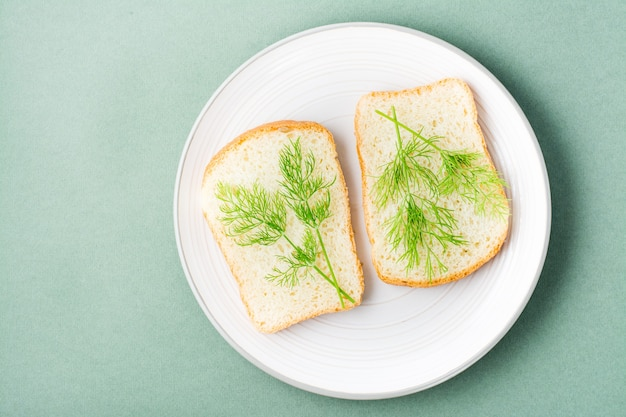 Kanapki z białego chleba i świeżego koperku na talerzu na zielonym tle. zioła witaminowe w zdrowej diecie. widok z góry