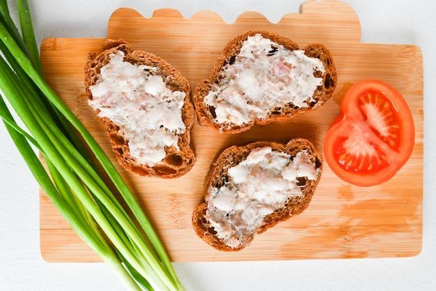 Kanapki z cebulą i pomidorami. upieczony tłuszcz rozmazany na bułce. ukraińskie jedzenie