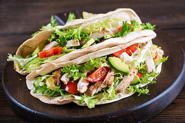 Kanapki z chleba pita z grillowanym mięsem z kurczaka, awokado, pomidorem, ogórkiem i sałatą podawane na drewnianym stole