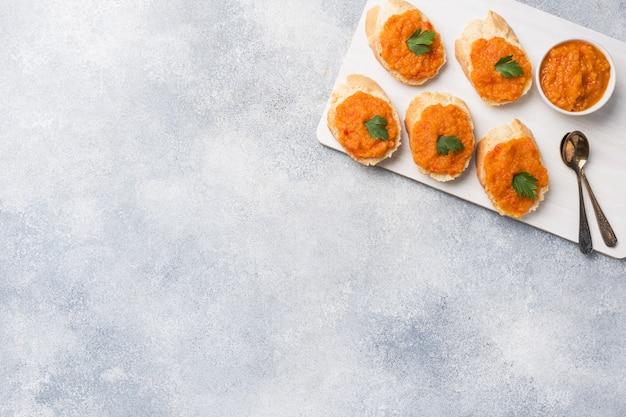 Kanapki z chlebem cukinia kawior pomidor cebula. domowe jedzenie wegetariańskie. copyspace.
