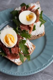 Kanapki z chlebem pełnoziarnistym, domowym serem, rukolą, szynką i jajkiem. zdrowa przekąska.