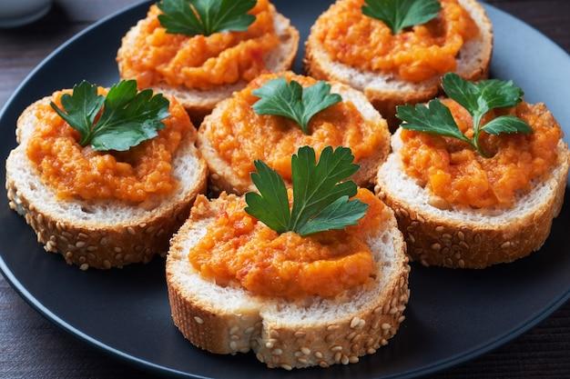 Kanapki z chlebem z cukinii i kawiorem z pomidorów cebula. domowe jedzenie wegetariańskie. warzywo duszone w puszkach. drewniana powierzchnia z bliska