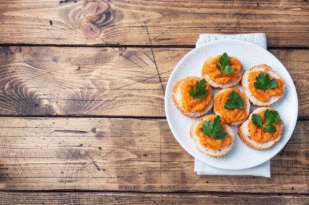 Kanapki z chlebem z cukinii i kawiorem z pomidorów cebula. domowe jedzenie wegetariańskie. warzywo duszone w puszkach. drewniane tło widok z góry, kopia przestrzeń