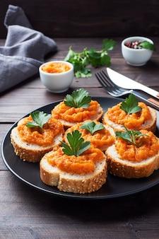 Kanapki z chlebem z cukinii i kawiorem z pomidorów cebula. domowe jedzenie wegetariańskie. warzywo duszone w puszkach. drewniane tło