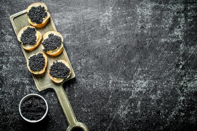 Kanapki z czarnym kawiorem na desce do krojenia i kawiorem w misce. na czarnym tle rustykalnym