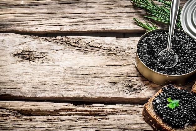 Kanapki z czarnym kawiorem, słoik kawioru i łyżka na drewnianym stole