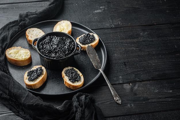 Kanapki z czarnym kawiorem z jesiotra, na czarnym tle drewnianego stołu z miejscem na tekst