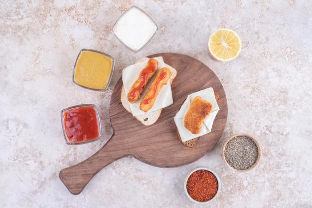 Kanapki z grillowaną kiełbasą z różnymi sosami.