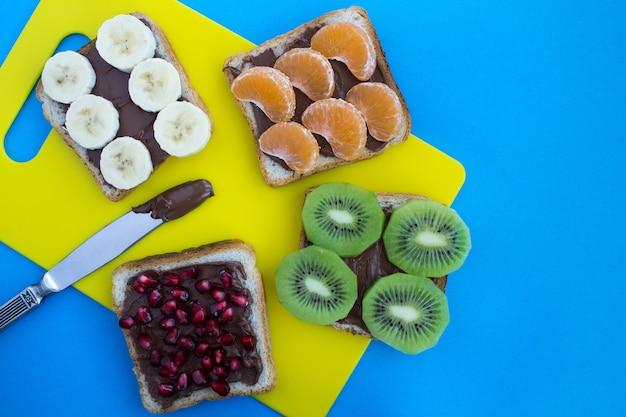 Kanapki z kremem czekoladowym i owocami na żółtym niebieskim tle.