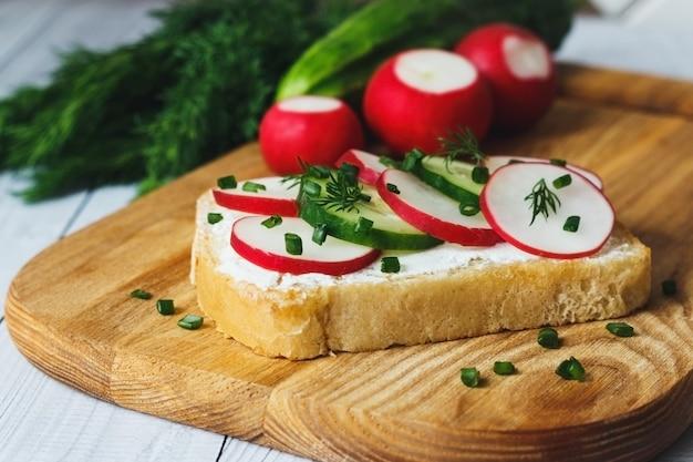Kanapki z kremowym serem ricotta, plastrami rzodkiewki i ogórka na drewnianej desce do krojenia