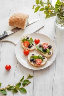 Kanapki z kremowymi pomidorami, oliwkami i bazylią na drewnianej tablicy