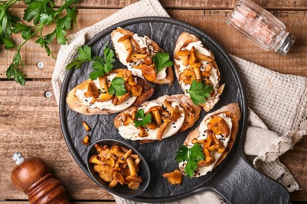 Kanapki z kurkami z serem. otwarta kanapka z kremowym serem, przyprawami, pieprzem i świeżą pietruszką na starym drewnianym tle. makieta. widok z góry.