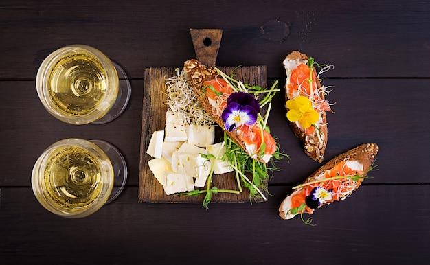 Kanapki z łososiem z twarogiem i microgreen na drewnianym stole. canape z łososiem.