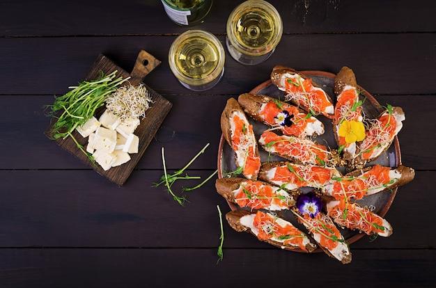 Kanapki z łososiem z twarogiem i microgreen na drewnianym stole.