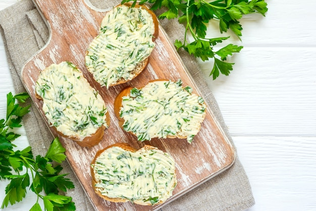 Kanapki z masłem zioła na desce do krojenia na białym tle drewnianych.