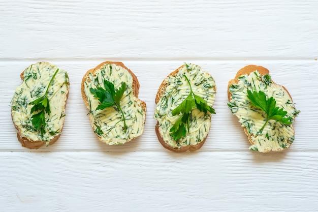 Kanapki z masłem ziołowym na białym tle drewnianych.
