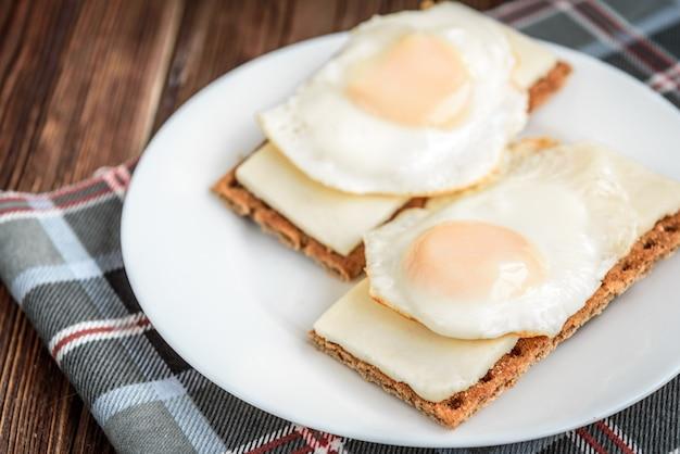 Kanapki z miękkim serem i jajkiem na chrupiącym chlebie żytnim na ciemnym drewnie.