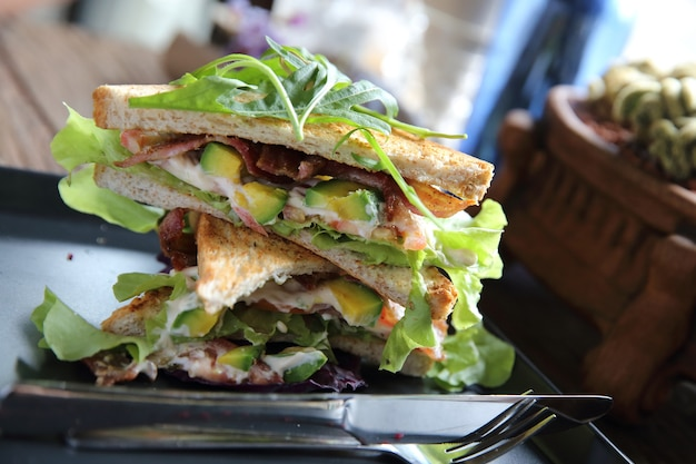 Kanapki z mięsem i warzywami na tle drewna