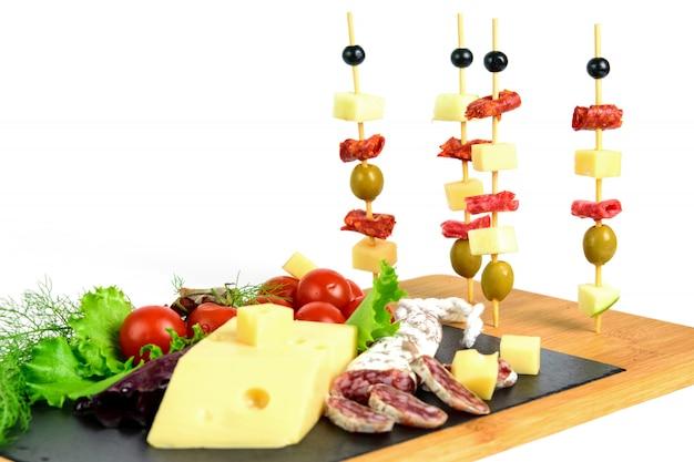 Kanapki z oliwkami, chorizo, salami, serem i jabłkiem na drewnianych patyczkach. produkty przekąskowe na tablicy tapas.