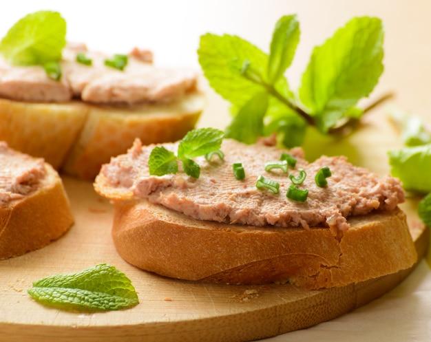 Kanapki z pastą i zieloną cebulą. podawany z gałązkami mięty.
