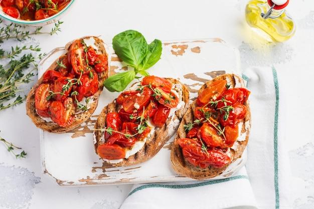Kanapki z pieczonymi pomidorkami i serem, tymiankiem, czosnkiem i ziołami na starym jasnym tle vintage. koncepcja śniadanie. widok z góry.