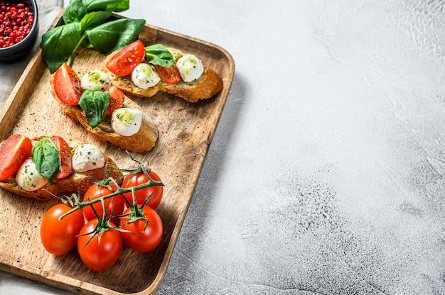 Kanapki z pomidorami, mozzarellą i bazylią. włoska przekąska, antipasto. szare tło. widok z góry. skopiuj miejsce