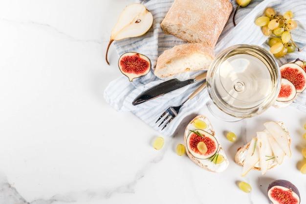 Kanapki z ricottą lub serem śmietankowym, ciabatta, świeżymi figami, gruszkami, winogronami, orzechami włoskimi i miodem na białym marmurowym stole, z widokiem na kieliszek do wina