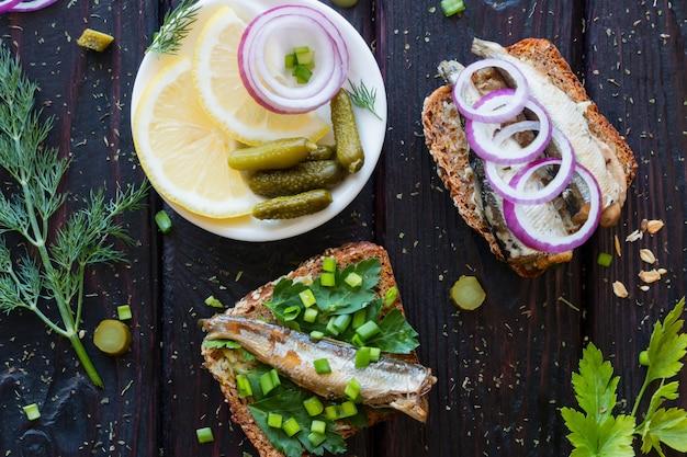 Kanapki z rybami i talerz z cebulą cytrynową i korniszonami
