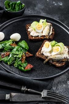 Kanapki z sardynkami, jajkiem, ogórkiem i serem śmietankowym, dodatki sałatkowe ze szpinakiem i suszonymi pomidorami. czarne tło. widok z góry