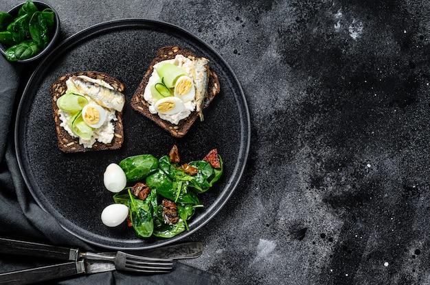 Kanapki z sardynkami, jajkiem, ogórkiem i serem śmietankowym, dodatki sałatkowe ze szpinakiem i suszonymi pomidorami.