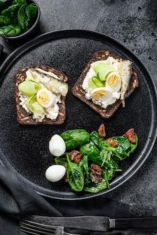 Kanapki z sardynkami, jajkiem, ogórkiem i serem śmietankowym, sałata ozdobiona szpinakiem i suszonymi pomidorami. czarne tło. widok z góry.