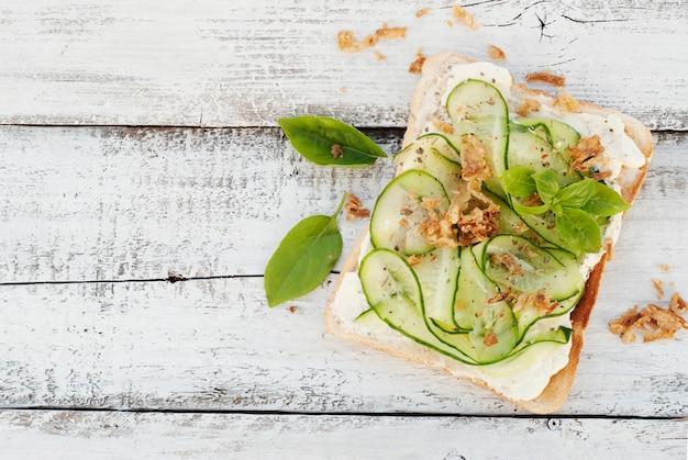 Kanapki z serem i plasterkami ogórka, liście bazylii, na drewnie. zdrowe przekąski