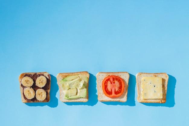 Kanapki z serem, pomidorem, bananem i awokado na niebieskiej powierzchni. pojęcie zdrowego odżywiania, śniadanie w hotelu, dieta. naturalne oświetlenie, twarde światło. leżał płasko, widok z góry.